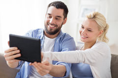 Smiling happy couple with tablet pc at home Stock Photos