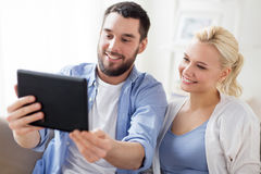 Smiling happy couple with tablet pc at home Royalty Free Stock Photos