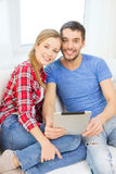 Smiling happy couple with tablet pc at home Royalty Free Stock Photography