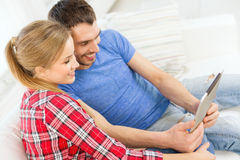 Smiling happy couple with tablet pc at home Stock Images