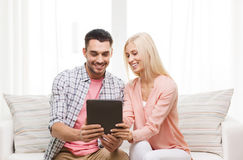 Smiling happy couple with tablet pc at home Stock Photography