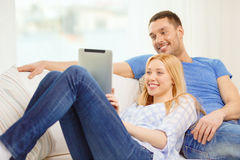 Smiling happy couple with tablet pc at home Stock Image
