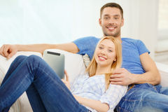 Smiling happy couple with tablet pc at home Royalty Free Stock Images