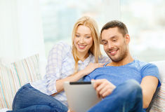 Smiling happy couple with tablet pc at home Royalty Free Stock Photo