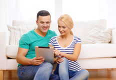 Smiling happy couple with tablet pc at home Royalty Free Stock Image