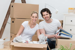 Smiling happy couple unpacking cardboard boxes Stock Photo