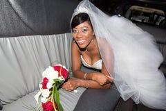 Happy dark skin black amercian bride in luxury limousine car for wedding stock photo