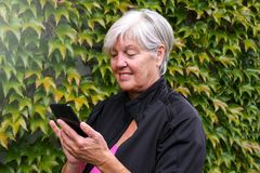 Smiling happy elderly woman talking outside on a mobile phone with nice autumn leaves stock images