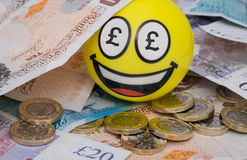 Smiling happy emoji covered in UK money. Money mad emoji sitting in pile of UK money stock images