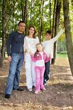 Smiling happy family of four in park stock photos