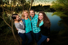 Smiling Happy Family by a Lake. A family of four pose and smile by a lake. Parents and two teen daughters, smile and laugh Royalty Free Stock Image