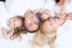 Smiling happy family lying together on a bed Royalty Free Stock Photography