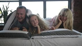 Smiling happy family posing under duvet in bedroom stock footage