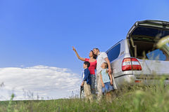 Smiling happy family and their car. Unsurpassed landscapes around us. Happy family standing near his car in field while mother pointing to sky Stock Photography