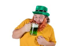 A smiling happy fat man in a leprechaun hat with green beer at studio. He celebrates St. Patrick. A smiling happy fat man in a leprechaun hat with green beer. He royalty free stock photos