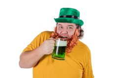 A smiling happy fat man in a leprechaun hat with green beer at studio. He celebrates St. Patrick royalty free stock photos