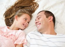 Smiling happy father with his little daughter child lying on the bed and having fun stock images