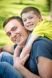 Smiling happy father and son hugging in the park Royalty Free Stock Photography