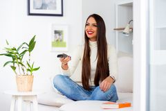 Smiling female enjoying her favourite TV show in the evening royalty free stock image