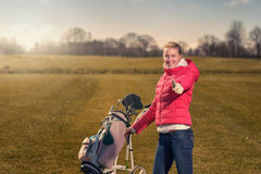Smiling happy female golfer giving a thumbs up. Smiling happy attractive young female golfer giving a thumbs up of success and approval as she pushes her golf Stock Photo