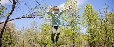 Happy boy playing and jumping outside. Smiling, happy five year old boy jumping outside on a spring day stock photo