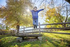 Smiling five year old boy jumping with red cape outside. Smiling, happy five year old boy wearing five shirt jumping and playing outside with red cape royalty free stock photos