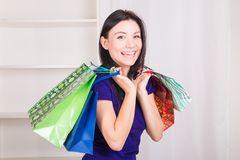 Smiling happy girl buys a bag gifts for Christmas Royalty Free Stock Images