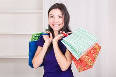 Smiling happy girl buys a bag gifts for Christmas Royalty Free Stock Photo