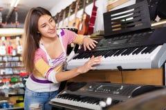 Smiling happy  girl choosing synthesizer Stock Photos