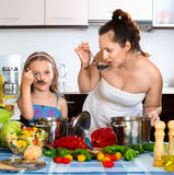 Smiling happy girl helping mother to cook Royalty Free Stock Photo