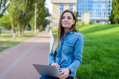 Smiling happy girl in jeans shirt using laptop for communication royalty free stock photography