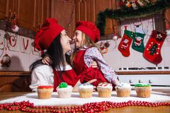 Festive red apron Christmas party dinner dessert peppermint cupcakes cream sugar sprinkling decoration girl new year chef chief. Smiling happy girl and mother in royalty free stock photos