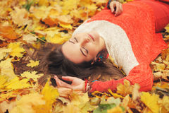 Smiling happy girl portrait, lying in autumn leaves, relax with closed eyes, dressed in fashion sweater Stock Photos