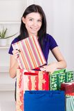 Smiling happy girl prepares bags gifts for Christmas Royalty Free Stock Images