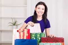 Smiling happy girl prepares bags gifts for Christmas Royalty Free Stock Photography