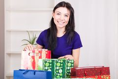 Smiling happy girl prepares bags gifts for Christmas Stock Photos