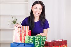 Smiling happy girl prepares bags gifts for Christmas Royalty Free Stock Photo