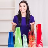 Smiling happy girl prepares bags gifts for Christmas Stock Image
