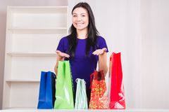 Smiling happy girl prepares bags gifts for Christmas Stock Photography