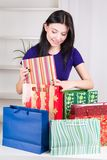 Smiling happy girl prepares bags gifts for Christmas Royalty Free Stock Photos