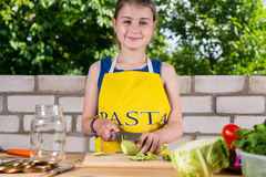 Smiling happy girl preparing fresh vegetables Royalty Free Stock Photos