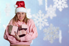Smiling happy girl in santa hat with gift boxes Royalty Free Stock Images