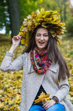 Smiling, happy girl wearing a wreath of maple leaves. In autumn park Stock Photography