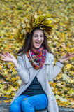 Smiling, happy girl wearing a wreath of maple leaves. In autumn park Royalty Free Stock Photography