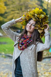 Smiling, happy girl wearing a wreath of maple leaves. In autumn park Stock Photos
