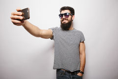 Smiling happy hipster man in sun glasses with beard taking selfie with mobile phone. Smiling happy hipster man in sun glasses with beard standing on white Royalty Free Stock Image