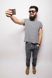 Smiling happy hipster man in sun glasses with beard taking selfie with mobile phone. Smiling happy hipster man in sun glasses with beard standing on white Royalty Free Stock Photography