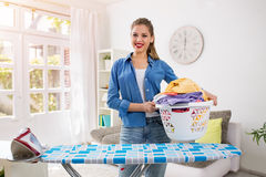 Smiling and happy housewife posing with iron and basket with cle Royalty Free Stock Photography