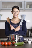 Smiling happy housewife preparing dinner Stock Image