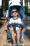 Smiling happy little baby boy spending time in the park playing with blue dragons Royalty Free Stock Images